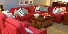 Pale blue walls contrast dramatically against the red sectional and recliners in this family-friendly living room.