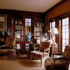 A pair of bergeres upholstered in faux tiger-skin stands by the window in the library-style living room.John Rosselli