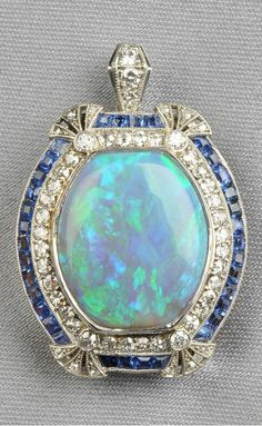 Platinum, Opal, Sapphire, and Diamond Pendant, bezel-set with an opal measuring approx. 18.00 x 15.00 x 4.50 mm, framed by old European- and single-cut diamonds, fancy-cut sapphire accents, millegrain details.