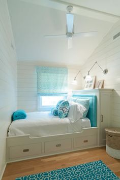 A narrow room makes great use of space with drawers built beneath a built-in bed.