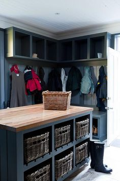 Large blue mudroom is equipped with a blue island fitted with shelves holding wicker baskets beneath a maple butcher block countertop. Mudroom Laundry Room, Small Laundry Rooms, Laundry Room Organization, Laundry Room Island, Laundry Baskets, Laundry Storage, Laundry Hacks, Kitchen Island, Vestibule