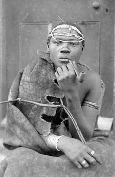 Africa | South Nguni man, possibly a shepherd, wearing a sheepskin kaross and smoking a typical Xhosa pipe.  His pipe cleaner is tucked into his beaded headdress.  ca 1880