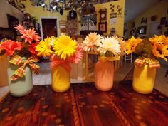 wired ribbon, spray painted mason jars, and colorful flowers make them cute & fun centerpieces