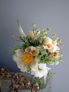 This arrangement of peonies, veronica, lisianthus, and clematis would make a charming wedding bouquet. The yellow flower pulls it all together.