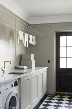 Traditional laundry room with checkered black and white tile flooring. Floor to ceiling wainscoting.