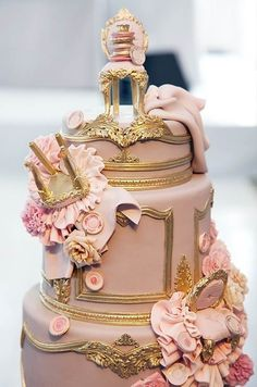 Fondant Louis XIV chairs tumbled down this ornately gilded wedding cake, by Cake Opera Co.