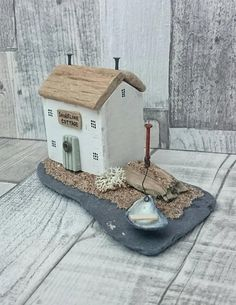 SHORELINE COTTAGE Handcrafted original artwork by DriftwoodSails Mixed Media Art created using reclaimed materials. This artwork is set on a large piece of tumbled sea slate found on the Kent coast. The wooden house is made from salvaged wood and painted in white chalk paint with a