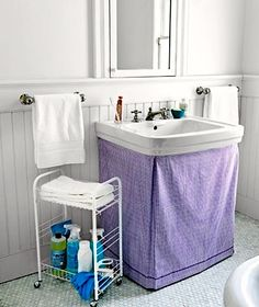 Small Bathroom Storage Tips   Conceal your sink! Pick out the fabric you want to use and attach it using velcro strips. It will hide the bins you store under the sink!