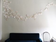 Wall art using thumbtacks and doilies. Super neat (and cheap!) idea...I think this example would pop more if it was on a colored wall like a spring green or something but its still cute.