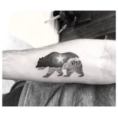 Double exposure bear tattoo on the right inner forearm.