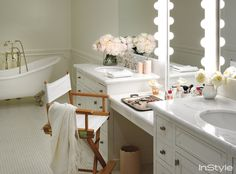 Lauren Conrad - Beautiful master bathroom boasts his and her vanities topped with white marble framing oval sinks paired with hook and spout faucets flanking drop-down vanity paired with lit vanity mirror paired with white director's chair.