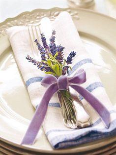 El lazo en color lavanda alrededor del ramo de hierbas realza esta simple pero elegante decoración de mesa.