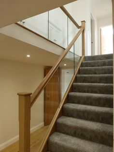 A modern staircase complete with glass balustrade. All other elements are oak finished with stop-chamfered newel posts. Staircase Glass Design, Glass Stair Balustrade, Wooden Staircase Railing, Staircase Design Modern, Steel Stair Railing, Home Stairs Design, Stair Railing Design, House Staircase, Balustrades