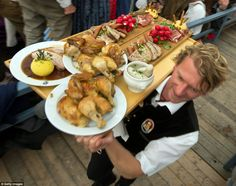 Line your stomachs: a waiter carries food for the hungry revellers who munched their way through 116 oxen and 57 calves last year - http://www.dailymail.co.uk/news/article-2427946/O-zapft--Beer-drinkers-Mecca-begins-Oktoberfest-kicks-Munich-traditional-cry.html