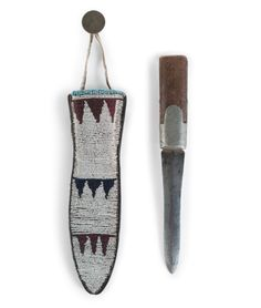 Blackfoot Beaded Knife Sheath with Knife, Exhibited at the Booth Western Art Museum, Cartersville, Georgia thread and sinew-sewn commercial leather, with beadworkin colors of rose, light blue, white, and dark blue; German silver button strung to hide thong, length 8.75 in.; and a heavily sharpened steel knife with wood and pewter handle, length 9.5 in. fourth quarter 19th century Provenance: From the Collection of John O. Behnken, (1950-2015) Georgia.   Cowan's  Auctions 04.08.17.