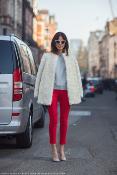 Alison in a white fur, grey sweater, red denim and silver and plastic heels.