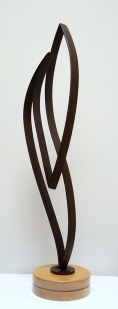 Hi, this is an abstract steel sculpture mounted to a wood base. The base is laminated hardwood finished with multiple coats of clear varnish