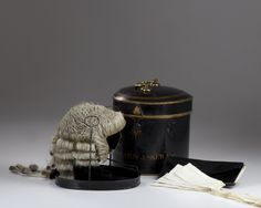 """English, black tole box with barristers wig """" H. Royston Askew Esq."""" the box made by Ravenscroft Law Wig and Robe makers Lincolns Inn London, original wig and 4 collars period handle..9.0″H case, 9.0″ at the cases widest point c.1790-1800"""