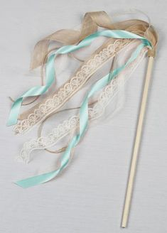 Incorporate this whimsical wand into your wedding with your flower girl, ring bearer, or wedding guests. Lace organza jute and David's Bridal exclusive ribbons are wrapped around a wooden rod to create the perfect airy stream of trims. Features and Facts:  Rod length: 19 inches.