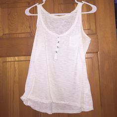 Super cute white tank top Gently worn, kind of see through with cute pearl like buttons. Will fit S/M. Tops Tank Tops