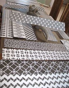 Cut wood to fit your staircase risers and then paint & stencil to your heart's content. Glue them on afterwards in the order you'd like and voila! -- much easier than stenciling in place on the stairs!