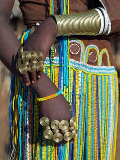"""The finery of a Datoga woman. The traditional attire of Datoga women includes beautifully tanned and decorated leather dresses and coiled brass ornaments of every description. Yellow and light blue are the preferred colours of the beads they wear. Scarification of the face is not uncommon among women and girls.The Datoga (known to their Maasai neighbours as the Mang'ati and to the Iraqw as Babaraig) live in northern Tanzania and are primarily pastoralists.  """