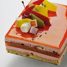 Dacquoise pistache inscrustée de groseilles et coiffée d'un croustillant blanc, compotée d'abricot, Génoise imbibée fruits rouges et bavaroise aux fruits rouges. Se déguste frais.