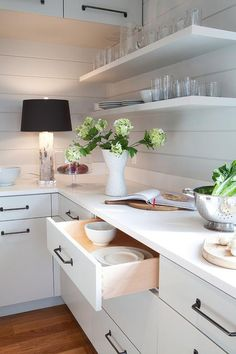 Chic cottage kitchen features white flat front cabinets adorned with oil rubbed bronze pulls topped with white quartz situated under white floating shelves lining a shiplap backsplash.