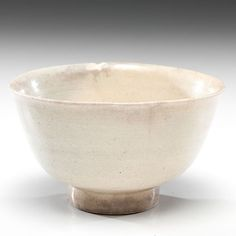 Tang Dynasty Pottery Bowl. Chinese, Tang dynasty. A footed bowl covered in a pale beige glaze throughout. Ht. 3.5 in.