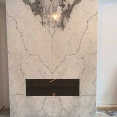 A sleek modern fireplace surrounded by timelessly gorgeous Statuario Marble book matched. Designed by Prestige Granite Design http://www.olympiatile-slabs.com/statuario.asp