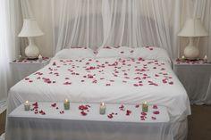 weiße Bettlaken, schiere Gardinen, rote Roseblätter und Kerzen