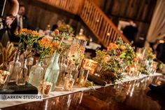 The glow of mercury glass candles clustered artistically with vintage bottles, books and other vintage accents come together to create a romantic feasting table setting courtesy of m. designs.  Olympias Valley Estate Wedding