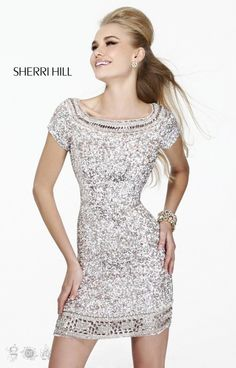 Sherri Hill 8521Wow! Sherri Hill 8521 is just breathtaking! This form fitting cocktail dress features a a squared neckline adorned in a ravishing design of beadwork and sequins. The neckline and short sleeves gives this dress a more modest look. The dress is fully embellished in sequins giving that WOW factor all they way. The hem features a unique design of beading in square shapes. Pair this dress with dazzling heels and you'll WOW the crowd!!