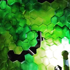 Green hexagons forming a textural surface.  .  .  #workshop #setbuilding #setconstruction #creativemanufacture #events #eventprofs #hexagons #light #green #dappled #pattern #glow #propmaking #props