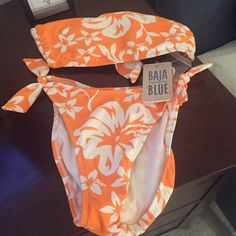NWT BajaBlue tangerine/mango & white Hawaii bikini NWT BajaBlue tangerine/mango &white Hawaii style print bikini.  Bandeau top ties in back with skinny straps (if you want) inner plastic hooks.  Bikini bottom has sanitary tag.  NEVER WORN.   Pattern and color reminiscent of 1950's-1960's Hawaii tiki themes.    Fabric content 84% nylon 16% spandex.  Very fun pattern -- wish it fit (but my size 4 days are behind me!) Baja Blue Swim Bikinis