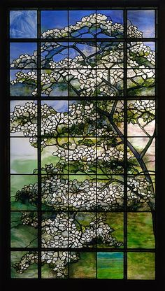 This window demonstrates Tiffany's true genius in glass. Its asymmetrical composition acknowledges his admiration for Japanese art, but nature was Tiffany's primary inspiration. The window convincingly conveys the appearance of a dogwood tree—the branches and blossoms seen behind a trellis—with a generalized spring landscape beyond