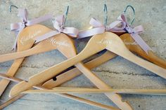 Great bridesmaids gift idea! wooden hangers with their name in calligraphy and a sweet bow at the top.