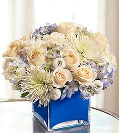 "Blue hydrangea, white roses, carnations, spider mums and button poms .  This vase measures 5""H x 5""D.  DIY appears to be: 2-3 spider mums, 6 carnations, 1-2 hydrangea, 3-5 garden roses, + poms (in shades of white and purple)"