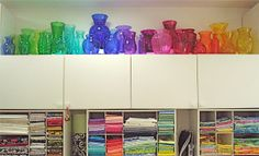 I like the collection of colored glass above her fabric stash.  Pretty rainbow!