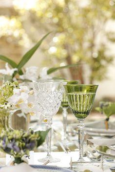 Sousplats, talheres, marcadores de lugar e descansos de talher em prata e taças em cristal transparentes e verdes completaram a mesa.