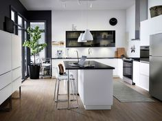 A large modern kitchen with white drawers, black smoked glass doors and a kitchen island.