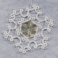 Little Ring Snowflake with Medallion Center.  Book:  Tatted Snowflakes by Vida Sunderman.  Thread: HH Snow White 601 size 20.  Medallion:  http://www.firemountaingems.com