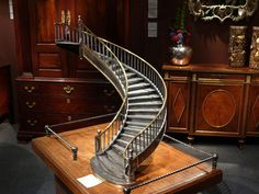 a late 19th century model of a spiral staircase constructed of polished cast iron and wrought iron, with brass handrails and on an oak parquetry floor platform base, c. 1880. (eloise moorhead's blog with LOTS of dollhouse action)
