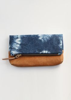 """This beauty is hand dyed and truly unique. Made with 10oz canvas and lined  in organic cotton canvas with a patch pocket. Bottom leather makes it more  substantial and the leather cord and heavy duty zipper made it super  durable.  Hand Dyed in Brooklyn by: Katrin Reifeiss. Read more about the maker.  Measures - 12.5"""" x 8"""" folded and 12.5"""" x 12.5"""" unfolded"""