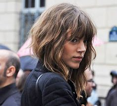 Wavy angled bob with bangs - I think it's just her collar that makes it look angled, but I like it!