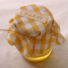 Jar of honey with yellow gingham cloth topper stamped with bees