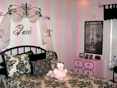 "Pink+and+white+stripes+are+the+perfect+background+for+this+French-inspired+design.+Iron+scrollwork+and+sheer+fabric+highlight+the+headboard+with+the+word+""Paris""+painted+over+it.+A+picture+of+the+Eiffel+Tower+hands+over+the+pink+dresser."