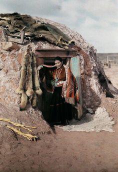 Navajo woman in front of her hogan