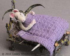 A poseable miniature felt mouse lies on a moss mattress in a bed made from twigs.