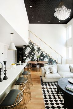 Open-plan living space with high ceilings, a staircase with floral wallpaper, a large chandelier, textured wallpaper on the ceiling and mixed material floors